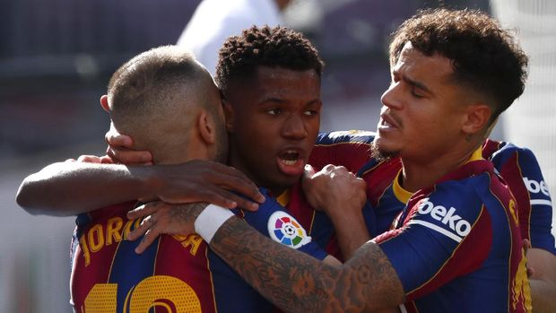 Barcelona's Ansu Fati celebrates with team mates scoring his side's first goal during the Spanish La Liga soccer match between FC Barcelona and Real Madrid at the Camp Nou stadium in Barcelona, Spain, Saturday, Oct. 24, 2020. (AP Photo/Joan Monfort)