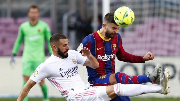 Barcelona's Gerard Pique fights for the ball against Real Madrid's Karim Benzema during the Spanish La Liga soccer match between FC Barcelona and Real Madrid at the Camp Nou stadium in Barcelona, Spain, Saturday, Oct. 24, 2020. (AP Photo/Joan Monfort)