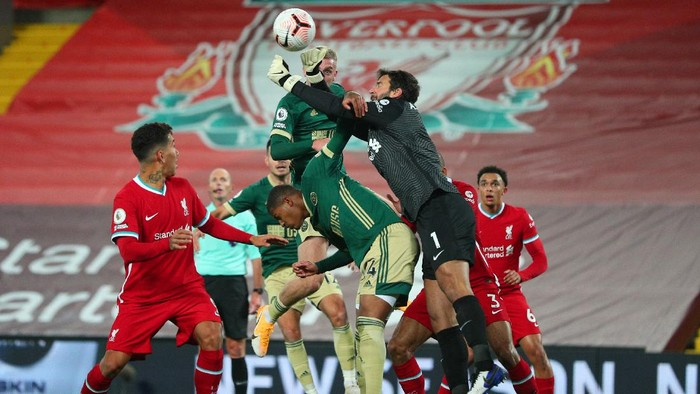 LIVERPOOL, ENGLAND - OCTOBER 24: Alisson Becker of Liverpool clears the ball under pressure from Oli McBurnie of Sheffield United during the Premier League match between Liverpool and Sheffield United at Anfield on October 24, 2020 in Liverpool, England. Sporting stadiums around the UK remain under strict restrictions due to the Coronavirus Pandemic as Government social distancing laws prohibit fans inside venues resulting in games being played behind closed doors. (Photo by Peter Byrne - Pool/Getty Images)