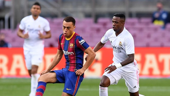 BARCELONA, SPAIN - OCTOBER 24: Sergino Dest of Barcelona  battles for possession with  Vinicius Junior of Real Madrid  during the La Liga Santander match between FC Barcelona and Real Madrid at Camp Nou on October 24, 2020 in Barcelona, Spain. Sporting stadiums around Spain remain under strict restrictions due to the Coronavirus Pandemic as Government social distancing laws prohibit fans inside venues resulting in games being played behind closed doors. (Photo by Alex Caparros/Getty Images)