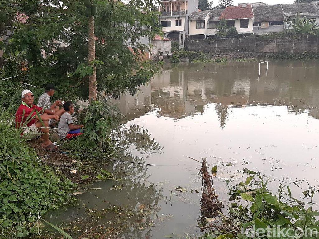 Serunya Warga Bogor Mancing Ikan di Lapangan Sepakbola yang Terendam Banjir