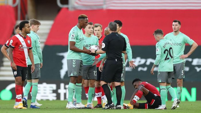 SOUTHAMPTON, ENGLAND - OCTOBER 25: Players of Everton speak with referee Kevin Friend after Lucas Digne of Everton is shown a red card during the Premier League match between Southampton and Everton at St Marys Stadium on October 25, 2020 in Southampton, England. Sporting stadiums around the UK remain under strict restrictions due to the Coronavirus Pandemic as Government social distancing laws prohibit fans inside venues resulting in games being played behind closed doors. (Photo by Naomi Baker/Getty Images)