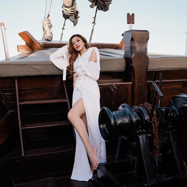 Seperti foto di atas, istri Gilang Widya Pramana ini terlihat berada di sebuah kapal besar sambil mengenakan gaun putih yang menjuntai panjang.