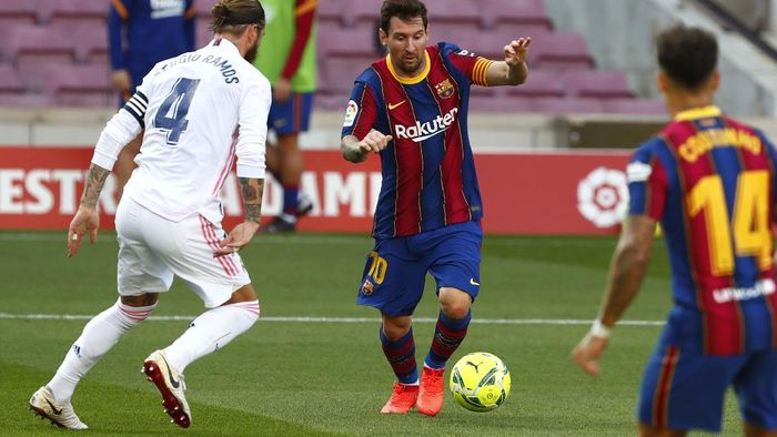 Barcelonas Lionel Messi fights for the ball against Real Madrids Sergio Ramos during the Spanish La Liga soccer match between FC Barcelona and Real Madrid at the Camp Nou stadium in Barcelona, Spain, Saturday, Oct. 24, 2020. (AP Photo/Joan Monfort)
