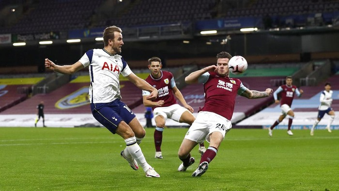 BURNLEY, ENGLAND - OCTOBER 26: Harry Kane of Tottenham Hotspur shoots under pressure from Kevin Long of Burnley  during the Premier League match between Burnley and Tottenham Hotspur at Turf Moor on October 26, 2020 in Burnley, England. Sporting stadiums around the UK remain under strict restrictions due to the Coronavirus Pandemic as Government social distancing laws prohibit fans inside venues resulting in games being played behind closed doors. (Photo by Jason Cairnduff - Pool/Getty Images)