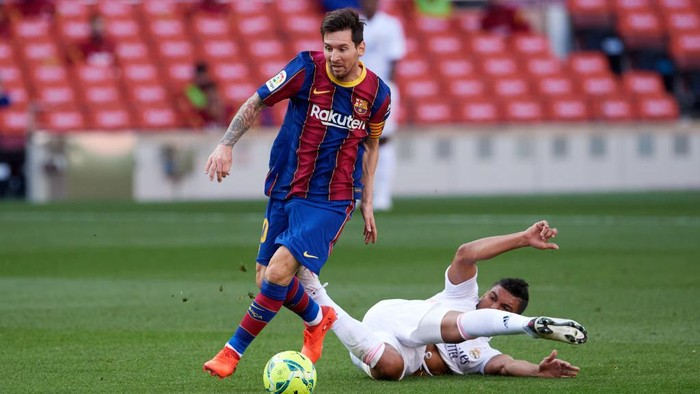 BARCELONA, SPAIN - OCTOBER 24: Carlos Casemiro of Real Madrid CF tackles Lionel Messi of FC Barcelona during the La Liga Santander match between FC Barcelona and Real Madrid at Camp Nou on October 24, 2020 in Barcelona, Spain. Sporting stadiums around Spain remain under strict restrictions due to the Coronavirus Pandemic as Government social distancing laws prohibit fans inside venues resulting in games being played behind closed doors. (Photo by Alex Caparros/Getty Images)