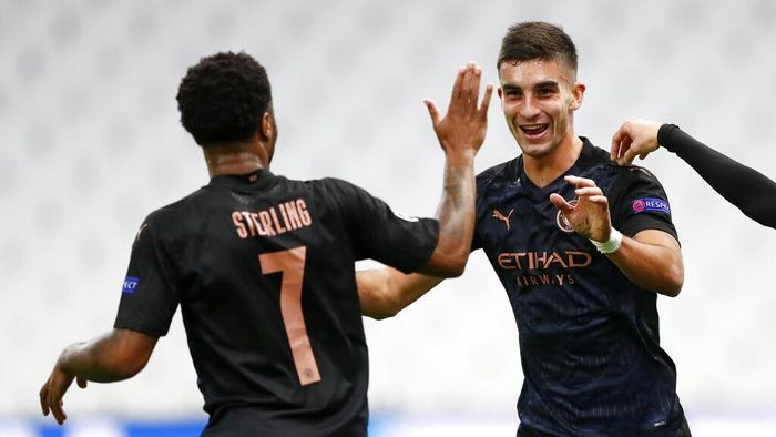 Manchester Citys Ferran Torres, right, is congratulated by teammate Raheem Sterling, left, after scoring his teams first goal during the Champions League Group C soccer match between Marseille and Manchester City at Stade Velodrome in Marseille, France, Tuesday, Oct. 27, 2020. (Guillaume Horcajuelo/Pool via AP)