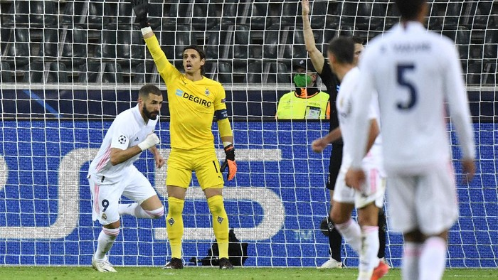 Real Madrids Karim Benzema, left, celebrates after scoring his sides opening goal during the Champions League group B soccer match between Borussia Moenchengladbach and Real Madrid at the Borussia Park in Moenchengladbach, Germany, Tuesday, Oct. 27, 2020. (AP Photo/Martin Meissner)