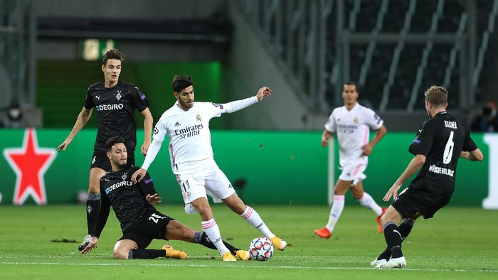 MOENCHENGLADBACH, GERMANY - OCTOBER 27: Marco Asensio of Real Madrid is challenged by Ramy Bensebaini of Borussia Moenchengladbach during the UEFA Champions League Group B stage match between Borussia Moenchengladbach and Real Madrid at Borussia-Park on October 27, 2020 in Moenchengladbach, Germany. Football Stadiums around Europe remain empty due to the Coronavirus Pandemic as Government social distancing laws prohibit fans inside venues resulting in fixtures being played behind closed doors. (Photo by Lars Baron/Getty Images)