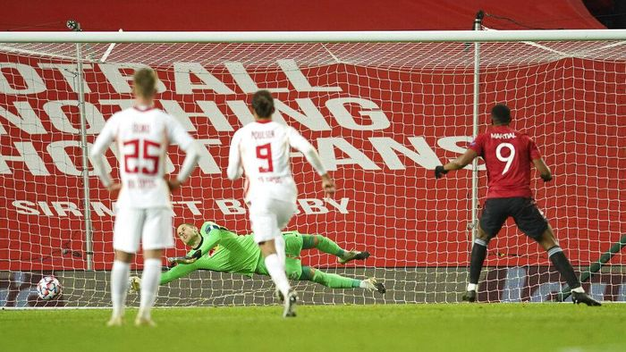 Leipzigs goalkeeper Peter Gulacsi fails to save the ball as Manchester Uniteds Anthony Martial, right, scores his sides fourth goal from the penalty spot during the Champions League group H soccer match between Manchester United and RB Leipzig, at the Old Trafford stadium in Manchester, England, Wednesday, Oct. 28, 2020. (AP Photo/Dave Thompson)