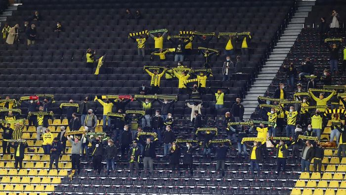DORTMUND, GERMANY - OCTOBER 24: Supporters of Dortmund cheer during the Bundesliga match between Borussia Dortmund and FC Schalke 04 at Signal Iduna Park on October 24, 2020 in Dortmund, Germany. A limited number of spectators (300) will be in attendance as Covid-19 pandemic restrictions are eased in Dortmund.  (Photo by Martin Rose/Getty Images)