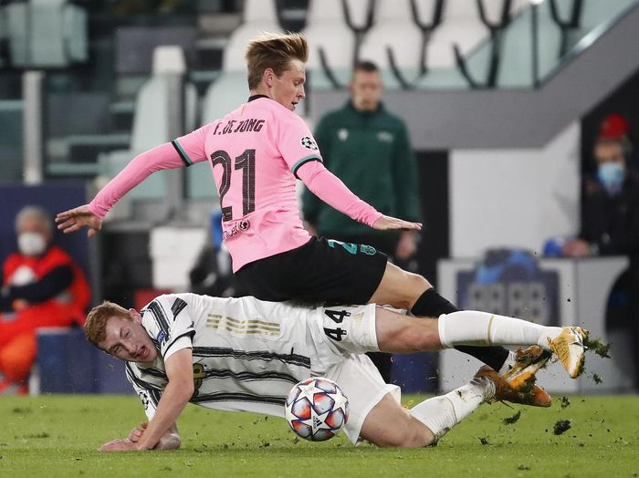 Juventus Dejan Kulusevski, bottom, challenges Barcelonas Frenkie de Jong during the Champions League group G soccer match between Juventus and Barcelona at the Allianz stadium in Turin, Italy, Wednesday, Oct. 28, 2020. (AP Photo/Antonio Calanni)