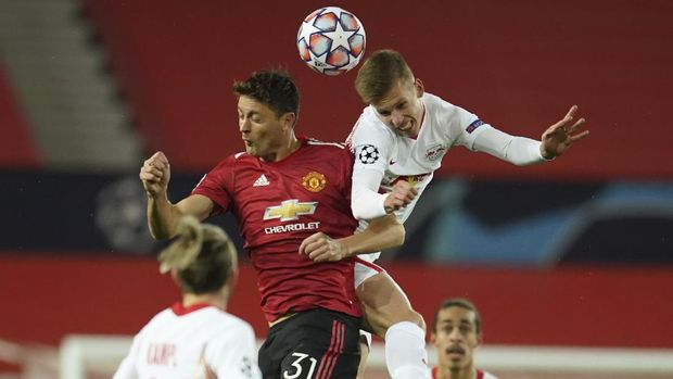 Manchester United's Nemanja Matic, left, jumps for the ball with Leipzig's Daniel Olmo during the Champions League group H soccer match between Manchester United and RB Leipzig, at the Old Trafford stadium in Manchester, England, Wednesday, Oct. 28, 2020. (AP Photo/Dave Thompson)