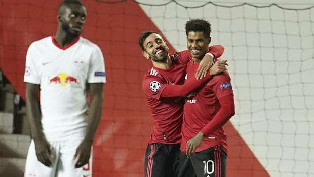 Manchester United's Marcus Rashford, right, celebrates with Manchester United's Bruno Fernandes after scoring his side's second goal during the Champions League group H soccer match between Manchester United and RB Leipzig, at the Old Trafford stadium in Manchester, England, Wednesday, Oct. 28, 2020. (AP Photo/Dave Thompson)