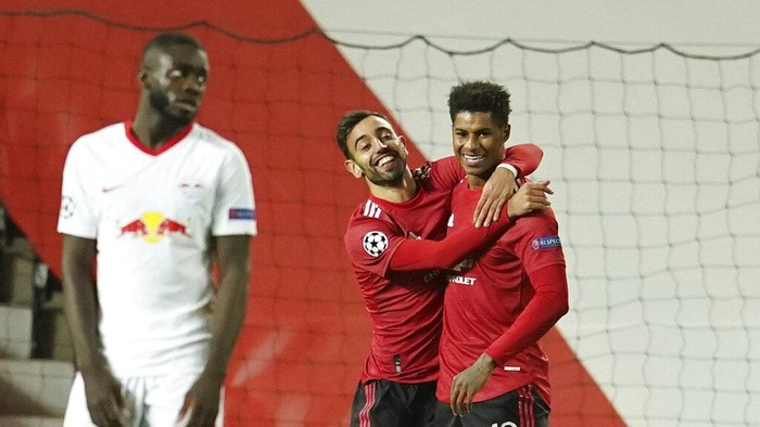 Manchester Uniteds Marcus Rashford, right, celebrates with Manchester Uniteds Bruno Fernandes after scoring his sides second goal during the Champions League group H soccer match between Manchester United and RB Leipzig, at the Old Trafford stadium in Manchester, England, Wednesday, Oct. 28, 2020. (AP Photo/Dave Thompson)