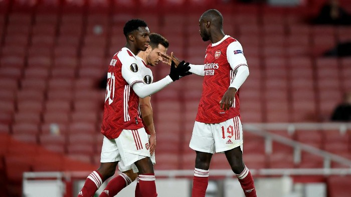 LONDON, ENGLAND - OCTOBER 29: Eddie Nketiah of Arsenal celebrates with teammate Cedric Soares and Nicolas Pepe of Arsenal after scoring his teams first goal during the UEFA Europa League Group B stage match between Arsenal FC and Dundalk FC at Emirates Stadium on October 29, 2020 in London, England. Sporting stadiums around the UK remain under strict restrictions due to the Coronavirus Pandemic as Government social distancing laws prohibit fans inside venues resulting in games being played behind closed doors. (Photo by Mike Hewitt/Getty Images)