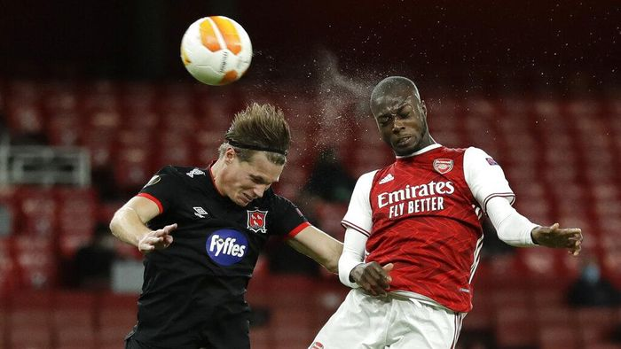 Arsenals Nicolas Pepe, right, and Dundalks Daniel Cleary compete to head the ball during the Europa League Group B soccer match between Arsenal and Dundalk at the Emirates Stadium in London, Thursday, Oct. 29. 2020. (AP Photo/Matt Dunham)
