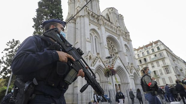 A French police officers stands near Notre Dame church in Nice, southern France, Thursday, Oct. 29, 2020. French President Emmanuel Macron has announced that he will more than double number of soldiers deployed to protect against attacks to 7,000 after three people were killed at a church Thursday. (Eric Gaillard/Pool via AP)