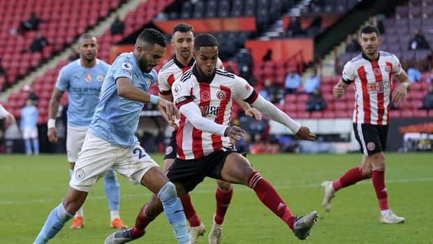 Manchester City's Riyad Mahrez, left, duels for the ball with Sheffield United's Max Lowe during the English Premier League soccer match between Sheffield United and Manchester City at Bramall Lane stadium in Sheffield, England, Saturday, Oct. 31, 2020. (Tim Keeton/Pool via AP)