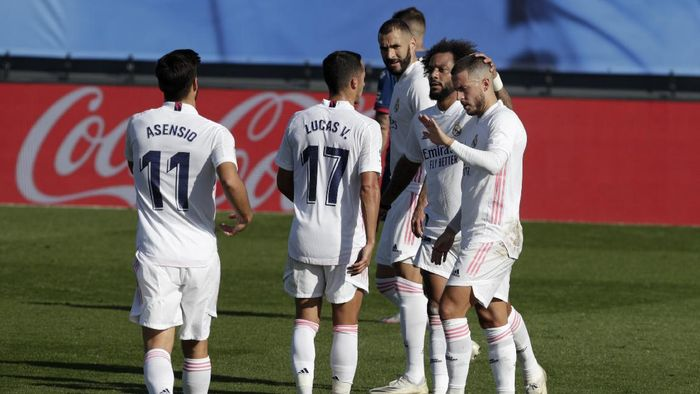 Real Madrids Eden Hazard, right, celebrates with teammates after scoring the opening goal during the Spanish La Liga soccer match between Real Madrid and Huesca at Alfredo di Stefano stadium in Madrid, Spain, Saturday, Oct. 31, 2020. (AP Photo/Manu Fernandez)