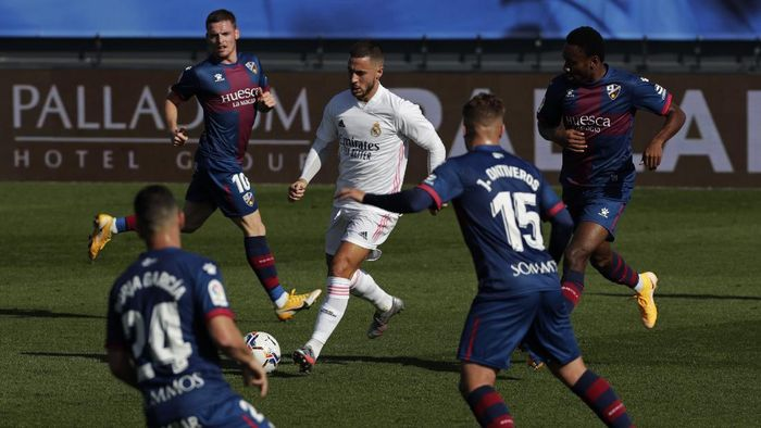 Real Madrids Eden Hazard, center, runs with the ball next to Huesca defenders during the Spanish La Liga soccer match between Real Madrid and Huesca at Alfredo di Stefano stadium in Madrid, Spain, Saturday, Oct. 31, 2020. (AP Photo/Manu Fernandez)