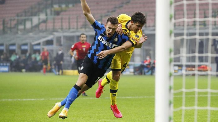 Inter Milans Ivan Perisic, left, challenges for the ball with Parmas Botond Balogh during the Serie A soccer match between Inter Milan and Parma at the San Siro Stadium, in Milan, Italy, Saturday, Oct. 31, 2020. (AP Photo/Antonio Calanni)