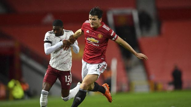 Manchester United's Harry Maguire, right, fights for the ball with Arsenal's Ainsley Maitland-Niles during the English Premier League soccer match between Manchester United and Arsenal at the Old Trafford stadium in Manchester, England, Sunday, Nov. 1, 2020. (Paul Ellis/Pool via AP)