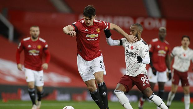 Manchester United's Harry Maguire, left, is challenged by Arsenal's Alexandre Lacazette during the English Premier League soccer match between Manchester United and Arsenal at the Old Trafford stadium in Manchester, England, Sunday, Nov. 1, 2020. (Phil Noble/Pool via AP)