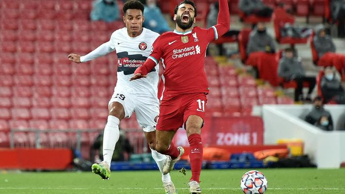 LIVERPOOL, ENGLAND - OCTOBER 27: Mohamed Salah of Liverpool is fouled by Paulinho of FC Midtjylland which leads to a penalty being awarded  during the UEFA Champions League Group D stage match between Liverpool FC and FC Midtjylland at Anfield on October 27, 2020 in Liverpool, England. Sporting stadiums around the UK remain under strict restrictions due to the Coronavirus Pandemic as Government social distancing laws prohibit fans inside venues resulting in games being played behind closed doors. (Photo by Peter Powell -