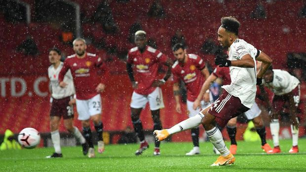 MANCHESTER, ENGLAND - NOVEMBER 01: Pierre-Emerick Aubameyang of Arsenal scores a penalty for his team's first goal  during the Premier League match between Manchester United and Arsenal at Old Trafford on November 01, 2020 in Manchester, England. Sporting stadiums around the UK remain under strict restrictions due to the Coronavirus Pandemic as Government social distancing laws prohibit fans inside venues resulting in games being played behind closed doors. (Photo by Shaun Botterill/Getty Images)