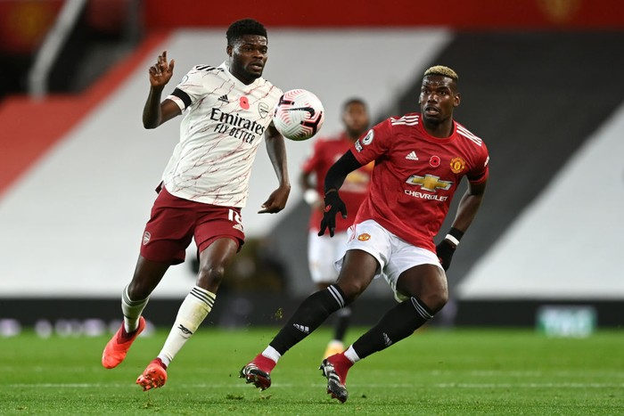MANCHESTER, ENGLAND - NOVEMBER 01: Thomas Partey of Arsenal is put under pressure by Paul Pogba of Manchester United during the Premier League match between Manchester United and Arsenal at Old Trafford on November 01, 2020 in Manchester, England. Sporting stadiums around the UK remain under strict restrictions due to the Coronavirus Pandemic as Government social distancing laws prohibit fans inside venues resulting in games being played behind closed doors. (Photo by Shaun Botterill/Getty Images)