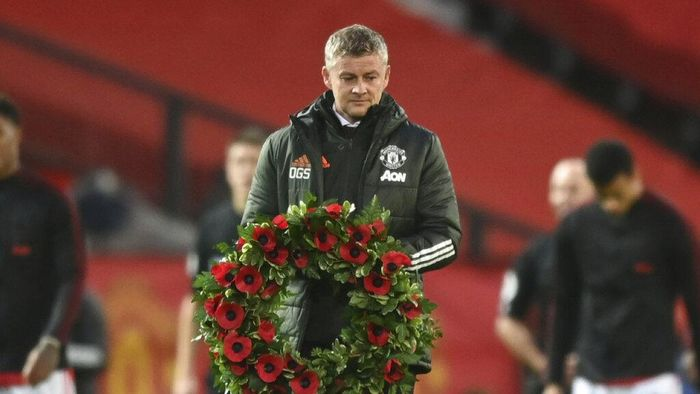 Manchester Uniteds manager Ole Gunnar Solskjaer carries out a wreath before kick-off in the English Premier League soccer match between Manchester United and Arsenal at the Old Trafford stadium in Manchester, England, Sunday, Nov. 1, 2020. (Shaun Botterill/Pool via AP)