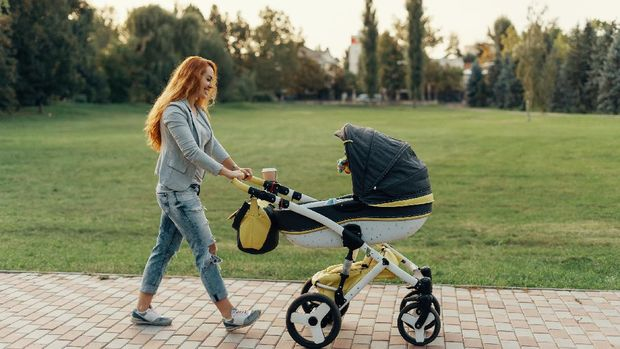 A young mother enjoying the park walk with her little child relaxing in his baby trolley.