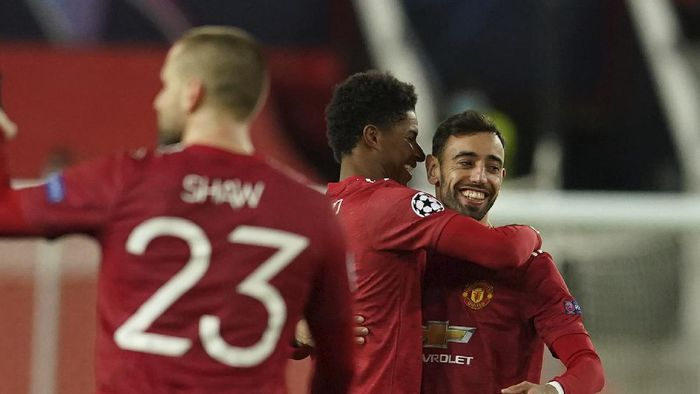 Manchester Uniteds Marcus Rashford, center, celebrates with Manchester Uniteds Bruno Fernandes after scoring his sides second goal during the Champions League group H soccer match between Manchester United and RB Leipzig, at the Old Trafford stadium in Manchester, England, Wednesday, Oct. 28, 2020. (AP Photo/Dave Thompson)