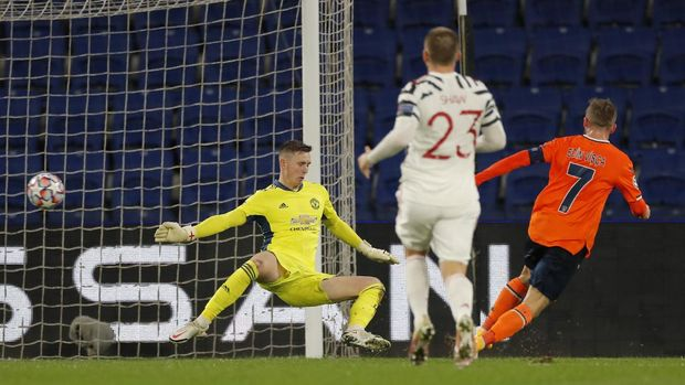 Manchester United's goalkeeper Dean Henderson, left, fails to save the ball as Basaksehir's Edin Visca, right, scores his side's second goal during the Champions League group H soccer match between Istanbul Basaksehir and Manchester United at the Fatih Terim stadium in Istanbul, Wednesday, Nov. 4, 2020. (AP Photo)