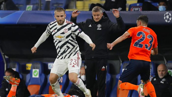 Manchester Uniteds manager Ole Gunnar Solskjaer, background, gestures as Manchester Uniteds Luke Shaw, left, fights for the ball with Basaksehirs Aziz Behich during the Champions League group H soccer match between Istanbul Basaksehir and Manchester United at the Fatih Terim stadium in Istanbul, Wednesday, Nov. 4, 2020. (AP Photo)