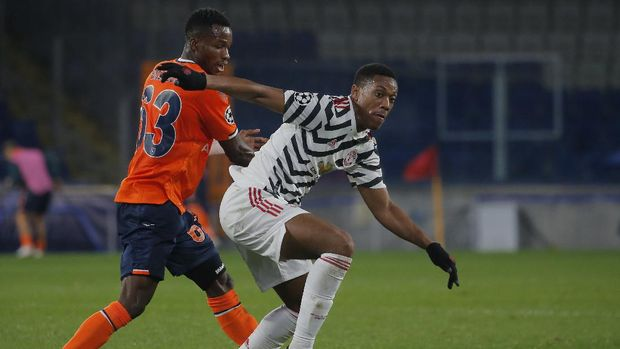 Manchester United's Anthony Martial, right, fights for the ball with Basaksehir's Boli Bolingoli-Mbombo during the Champions League group H soccer match between Istanbul Basaksehir and Manchester United at the Fatih Terim stadium in Istanbul, Wednesday, Nov. 4, 2020. (AP Photo)