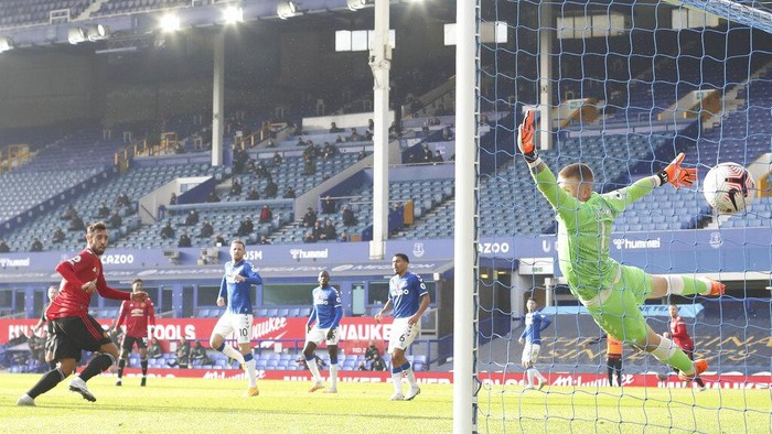 Manchester Uniteds Bruno Fernandes, left, scores his sides opening goal during the English Premier League soccer match between Everton and Manchester United at the Goodison Park stadium in Liverpool, England, Saturday, Nov. 7, 2020. (Carl Recine/Pool via AP)