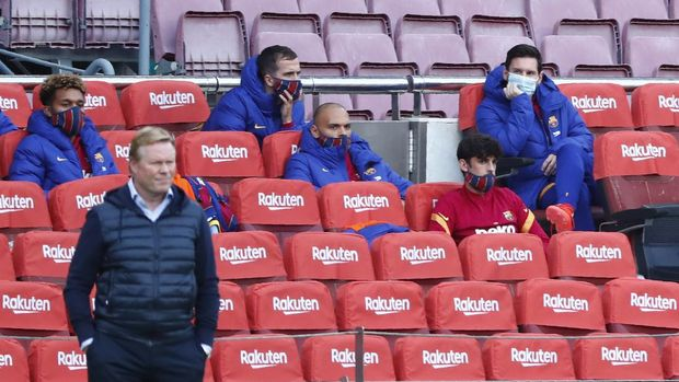 Barcelona's Lionel Messi, right, sits on the bench as Barcelona's head coach Ronald Koeman stands on the side line during the Spanish La Liga soccer match between FC Barcelona and Betis at the Camp Nou stadium in Barcelona, Spain, Saturday, Nov. 7, 2020. (AP Photo/Joan Monfort)