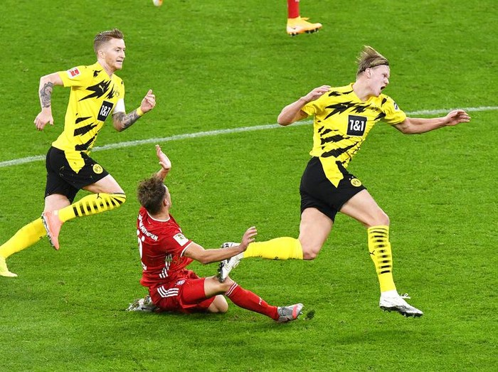 Dortmunds Marco Reus, left, Dortmunds Erling Haaland, right, and Bayerns Joshua Kimmich challenge for the ball during the German Bundesliga soccer match between Borussia Dortmund and Bayern Munich in Dortmund, Germany, Saturday, Nov. 7, 2020. (AP Photo/Martin Meissner, Pool)