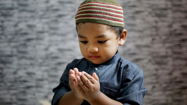A Muslim young man is putting both palms together (Muslim way of praying) at home in Malaysia. He is wearing 'baju Melayu', a traditional Muslim menswear.