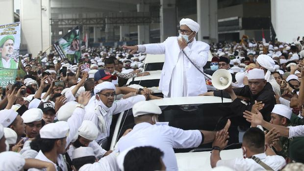 Indonesian Islamic cleric and the leader of Islamic Defenders Front Rizieq Shihab, center, speaks to his followers upon arrival from Saudi Arabia at Soekarno-Hatta International Airport in Tangerang, Indonesia, Tuesday, Nov. 10, 2020. Thousands of followers of the firebrand cleric joyfully welcomed him at an the airport as he returned home from a 3-year exile in Saudi Arabia after criminal charges including a pornography case were dropped. (AP Photo)