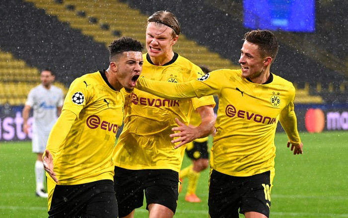 DORTMUND, GERMANY - OCTOBER 28: Jadon Sancho of Borussia Dortmund celebrates with teammates Thorgan Hazard and Erling Haaland  after scoring his teams first goal from the penalty spot during the UEFA Champions League Group F stage match between Borussia Dortmund and Zenit St. Petersburg at Signal Iduna Park on October 28, 2020 in Dortmund, Germany. Sporting stadiums around Dortmund remain under strict restrictions due to the Coronavirus Pandemic as Government social distancing laws prohibit fans inside venues resulting in games being played behind closed doors. (Photo by Lukas Schulze/Getty Images)