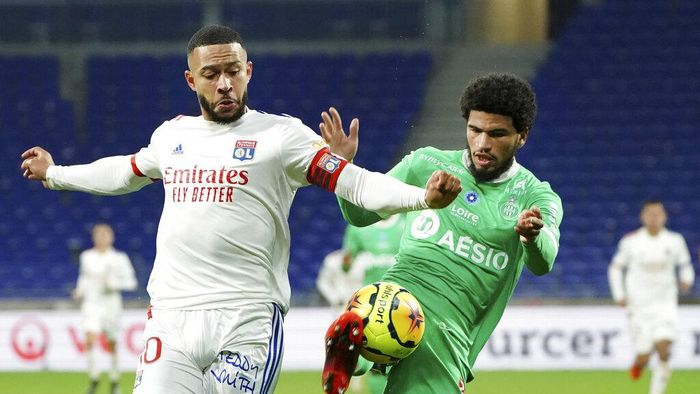 Lyons Memphis Depay, left, challenges for the ball with Saint-Etiennes Charles Nathan Abi, right, during the French League One soccer match between Lyon and Saint-Etienne in Decines, near Lyon, central France, Sunday, Nov. 8, 2020. (AP Photo/Laurent Cipriani)