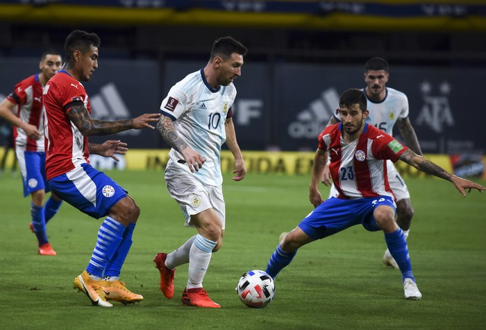 Argentinas Lionel Messi, center, and Paraguays Dario Lezcano, left, battle for the ball during a qualifying soccer match for the FIFA World Cup Qatar 2022 in Buenos Aires, Argentina, Thursday, Nov. 12, 2020.(Marcelo Endelli, Pool via AP)
