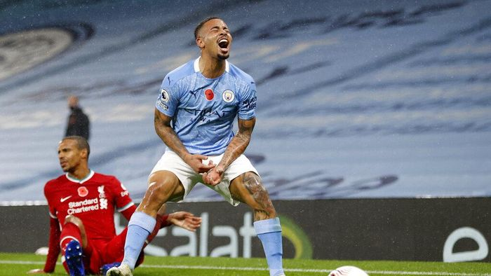 Manchester Citys Gabriel Jesus reacts following a clash with Liverpools Joel Matip, in the background, during the English Premier League soccer match between Manchester City and Liverpool at the Etihad stadium in Manchester, England, Sunday, Nov. 8, 2020. (Clive Brunskill/Pool via AP)