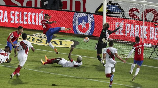 Chile's Arturo Vidal, center above, scores his side's second goal against Peru during a qualifying soccer match for the FIFA World Cup Qatar 2022 in Santiago, Chile, Friday, Nov. 13, 2020. (AP Photo/Esteban Felix)