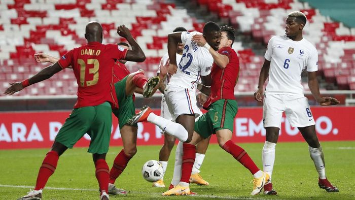 Frances Marcus Thuram, center, tries to back heel the ball during the UEFA Nations League soccer match between Portugal and France at the Luz stadium in Lisbon, Saturday, Nov. 14, 2020. (AP Photo/Armando Franca)