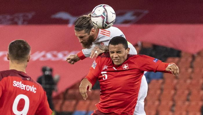 Spains Sergio Ramos, top, fights for a header with Switzerlands Manuel Akanji during the UEFA Nations League soccer match between Switzerland and Spain at the St. Jakob-Park stadium in Basel, Switzerland, Saturday Nov. 14, 2020. (Georgios Kefalas/Keystone via AP)