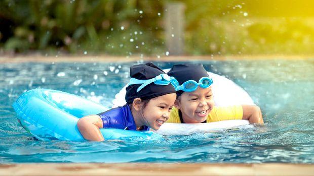 two asian little girls having fun to swim in swimming pool together